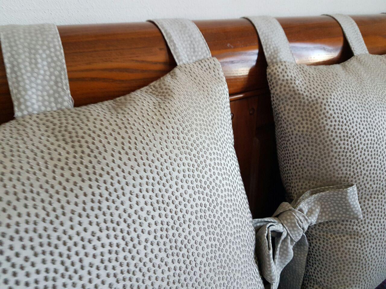 cuscini con fiocchi fissati su testata liscia