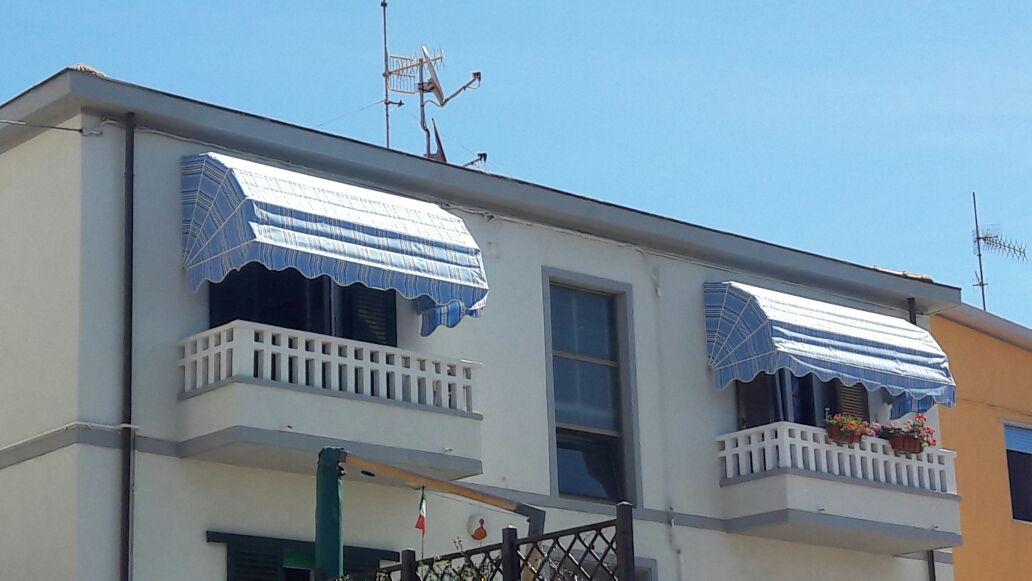 tenda a bracci a righe blu su terrazzo palazzina esterno
