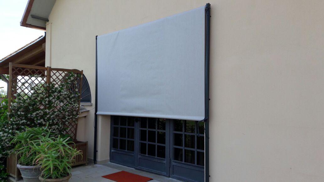 tenda a caduta con profili in antracite per portafinestra su giardino interno
