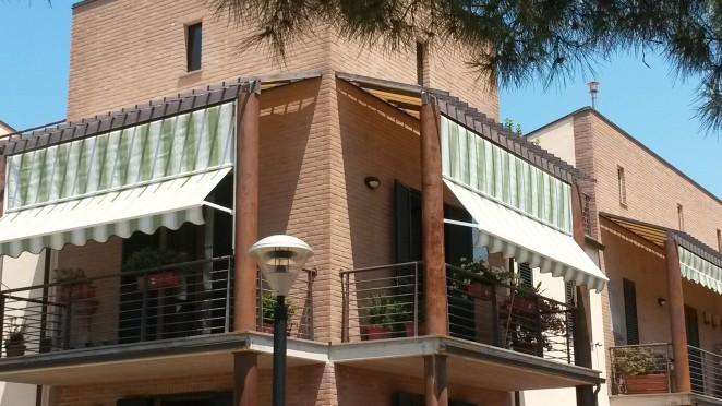 tende da sole a caduta con braccetti in tessuto a righe verdi e bianche per condominio