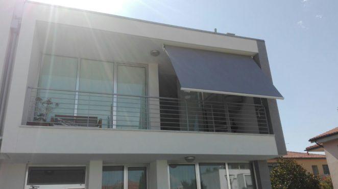tenda a bracci a tinta unita grigia su misura per schermatura di una parte del terrazzo