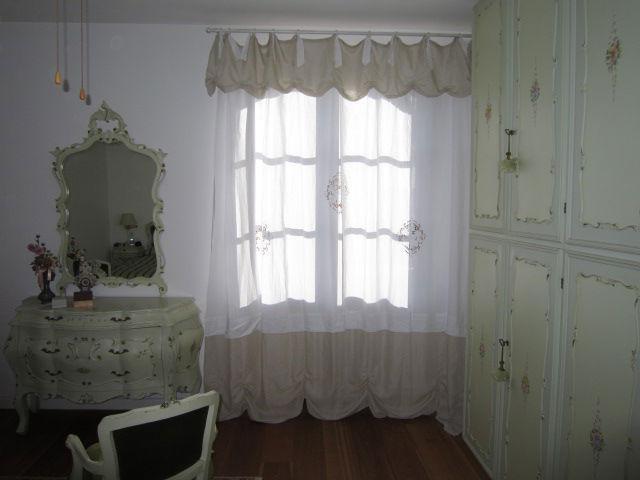 tenda classica bianca con laccetti e drappeggio in tessuto ecrù in camera stile veneziano