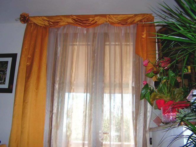 tende arricciate su bastone con drappeggi in seta arancio su bastone in ferro battuto